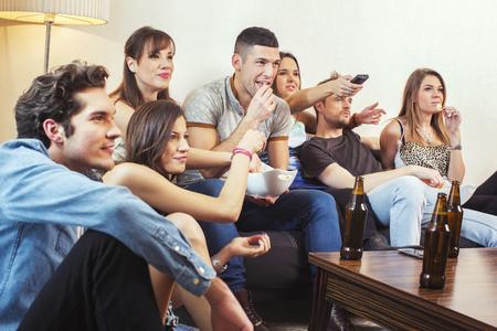pareja viendo television: Grupo de amigos viendo la televisión en casa