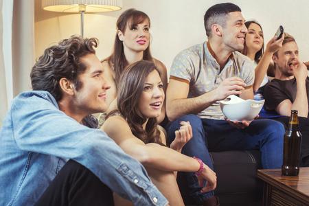 집에서 TV를 시청하는 친구 그룹 스톡 콘텐츠