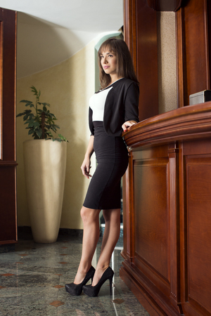 standing reception: Young woman standing by the reception desk