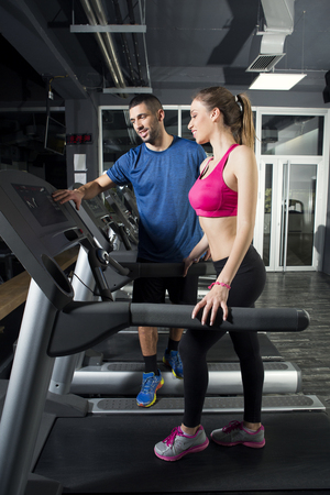 Young woman on treadmill, with instructor