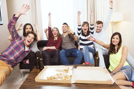 テレビの試合を観戦し、応援の友人のグループ 写真素材