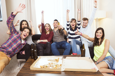 Group of friends watching TV match and cheering Stockfoto