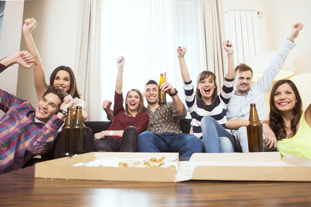 Group of friends watching TV match and cheering Stock Photo