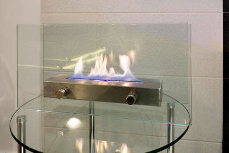 contemporaneous: Portable glass fireplace on a glass table Stock Photo
