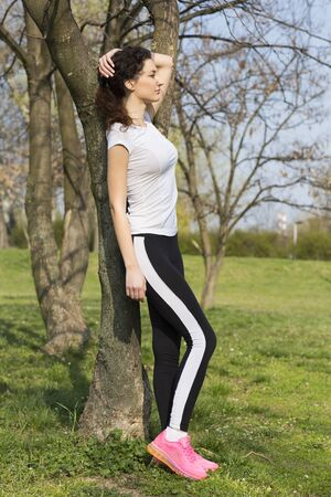 workouts: Fitness girl resting against a tree in between workouts
