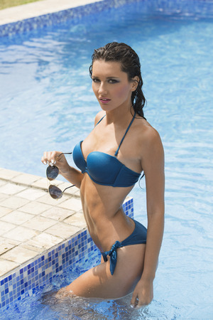 navy blue suit: Beautiful sensual woman in swimming pool Stock Photo