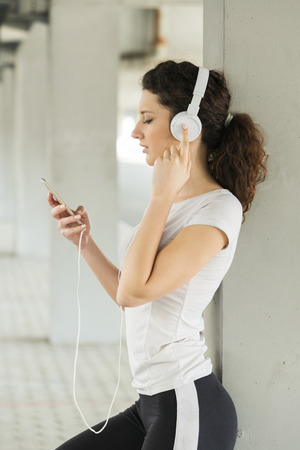 workouts: Fitness girl listening to music between workouts