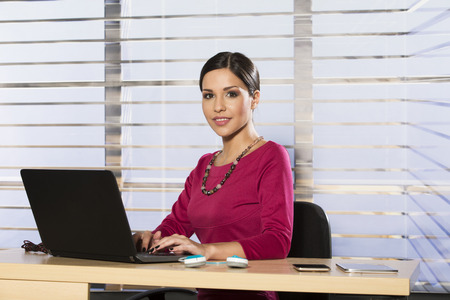 at her desk: Young businesswoman at her desk