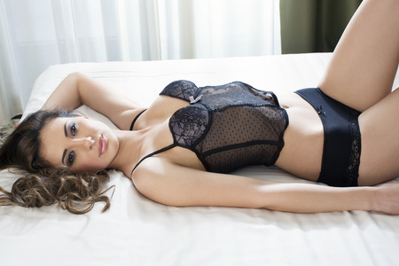 Beautiful woman posing in bed in lingerie Stock Photo