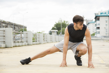 stretches: Fit young man doing stretches outdoors Stock Photo