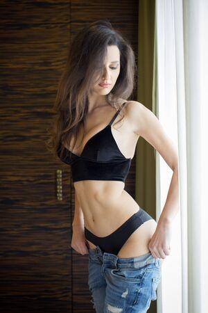 jeans apretados: Mujer joven que pone la ropa en la mañana Foto de archivo