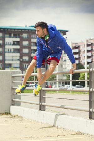 salto de valla: joven apuesto atleta salta sobre la cerca Foto de archivo