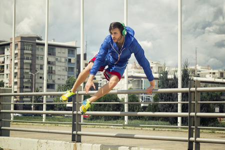 salto de valla: Handsome young athlete jumping over the fence