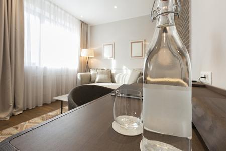 vasos de agua: Botella de agua en la mesa de madera en la habitación del hotel