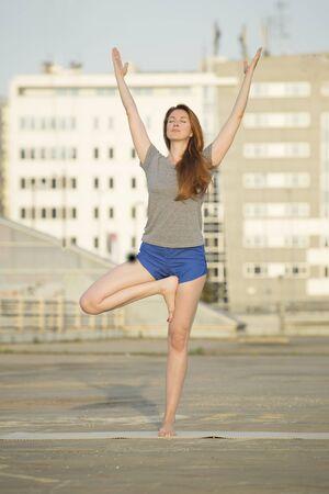neighbourhood: Young woman doing yoga outdoors in an urban neighbourhood