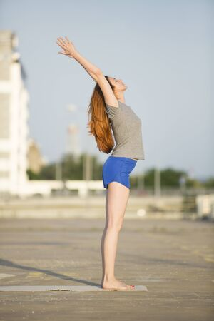 neighbourhood: Woman practicing yoga in an urban neighbourhood Stock Photo