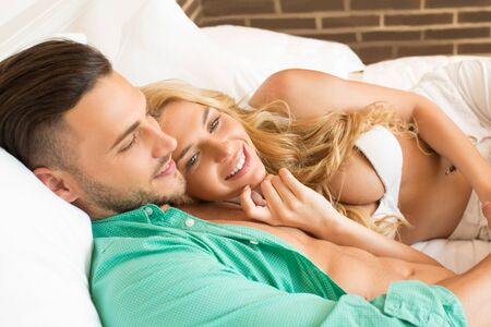 seminude: Attractive couple relaxing together in bed