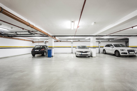 parking lot interior: Underground parking lot, interior with a few parked cars. Stock Photo