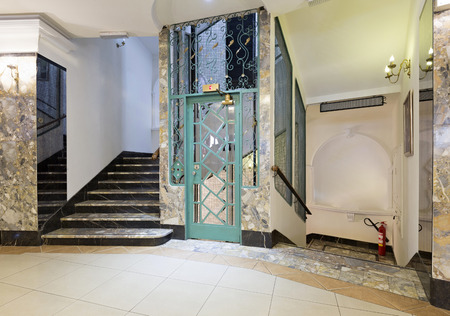 metallic stairs: Interior of a corridor with passenger lift and marble stairs