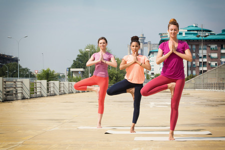 vriksasana: Beautiful women doing yoga outdoors in an urban neighbourhood Stock Photo