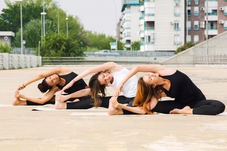 Beautiful women doing yoga outdoors in an urban neighbourhood Stock Photo