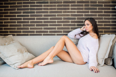woman on couch: Beautiful young woman on couch at home Stock Photo