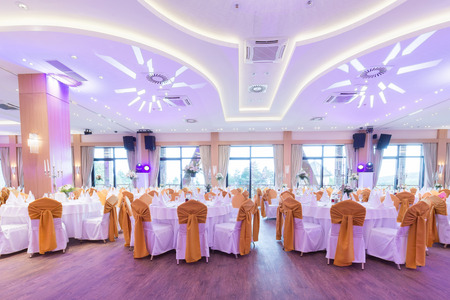 Wedding hall or other function facility with colorful ceiling lights set for fine dining  Stock Photo