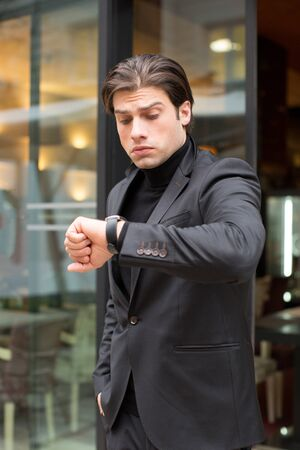 Handsome young man looking at his watch