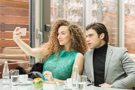 Man and woman making selfie at the cafe