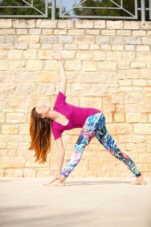 Woman  doing yoga exercise. Revolved Triangle Pose, Parivrtta Trikonasana Stock Photo