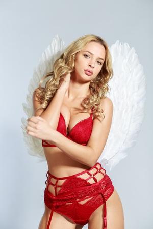 Hübsche Frau im roten BH und in den Unterwäsche schwarze Strümpfe Strümpfe Flügel