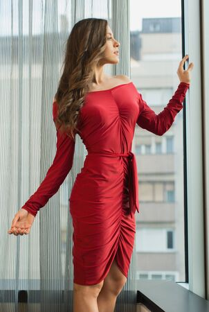 Beautiful brunette  woman looking through window