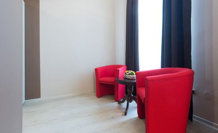 Hotel apartment interior with two red armchairs