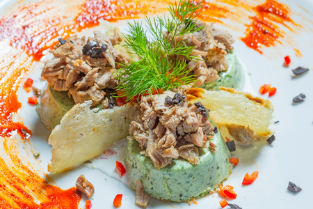 Chopped beef with green pate served on white plate