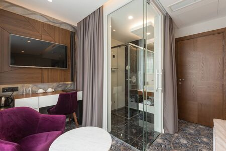 Interior of a luxury hotel apartment room with glass wall bathroom