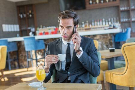 Handsome young businessman talking on the cell phone in hotel cafe