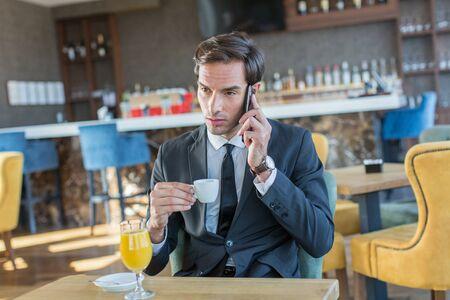Przystojny młody biznesmen rozmawia przez telefon komórkowy w hotelowej kawiarni