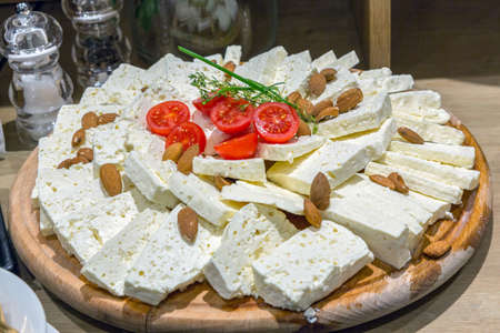 Goat cheese with almonds served on wooden board