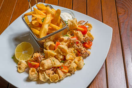 Crispy calamari rings with french fries and sauce