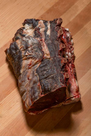 Raw dry aged ribs on wooden board