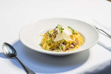 Tagliatelle pasta with cheese and chicken meat served on a white plate Standard-Bild