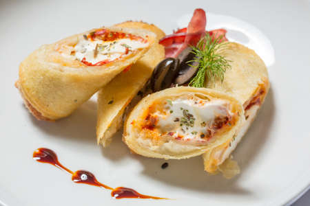 Salami and cream cheese breakfast roll served on white plate
