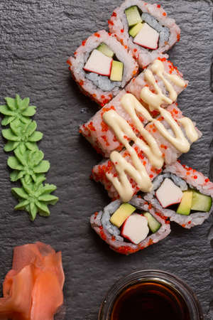 Uramaki sushi rolls with shrimp, cucumber topped with sauce and  caviar