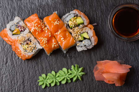 Smoked salmon sushi roll served on black stone
