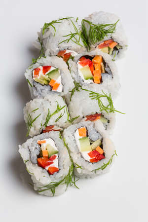 Sushi rolls with carrot, cucumber and cream-cheese in chopped dill Standard-Bild