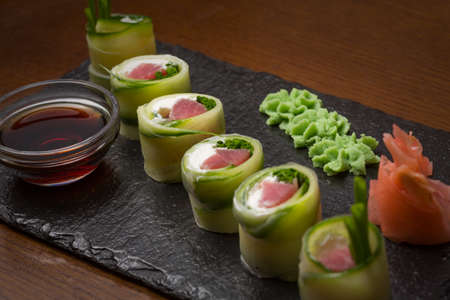 Cucumber rolls with salmon, cream cheese served on black stone