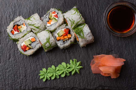 Sushi rolls with carrot, cucumber and cream-cheese in chopped dill served on black stone with wasabi Standard-Bild