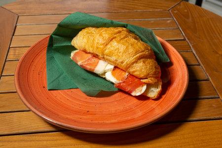 Croissant sandwich with prosciutto and cheese Standard-Bild