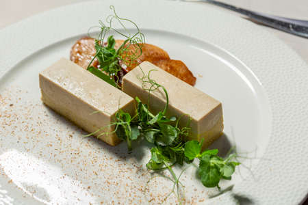 Goose liver pate served on a white plate