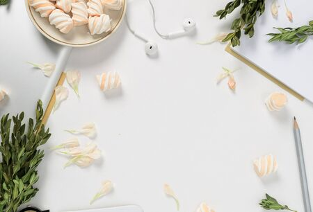 Workspace with tablet, flower petals, pencil, green branches and marshmallows on white background. top view 스톡 콘텐츠